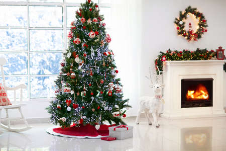 Decorated room with Christmas tree and fireplace. Xmas presents and gifts on holiday eve. Lights, fir garland with baubles and ornaments and reindeer figure. Family home decoration.