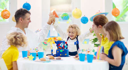 Kids space theme birthday party with cake and cupcakes. Rocket, solar system planet and astronaut decoration for child event. Little boy, friends and parents blowing candles and opening presents. Stock Photo