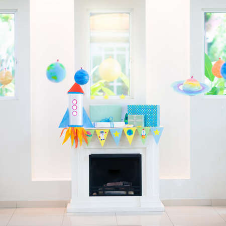 Space theme kids birthday party. Present and gift box on fireplace with banner and balloon. Children event with astronaut, rocket, planets of solar system decoration. Family festive celebration.