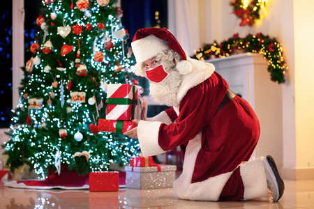Santa Claus in face mask brings presents at Christmas tree and fireplace. Safe Xmas celebration during coronavirus outbreak. Winter holidays in covid-19 lockdown. Gifts for kids.