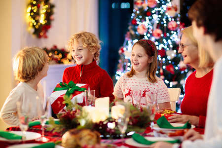 Family with children eating Christmas dinner at fireplace and decorated Xmas tree. Parents and kids enjoy festive meal. Winter holidays celebration and food. Grandmother cooking roasted turkey. Stockfoto