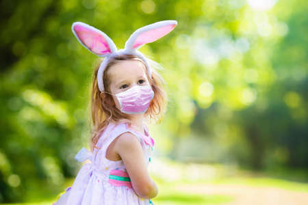 Little girl in face mask having fun on Easter egg hunt in outbreak. Kids in bunny ears and rabbit costume in pandemic celebration. Children with colorful eggs. Safe celebration. Banque d'images