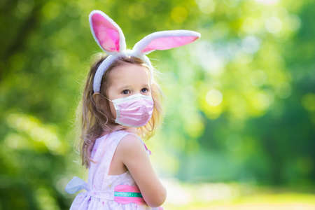 Little girl having fun on Easter egg hunt. Kids in bunny ears and rabbit costume. Children with colorful eggs in a basket. Toddler kid playing outdoor. Child holding blank white board for your text.
