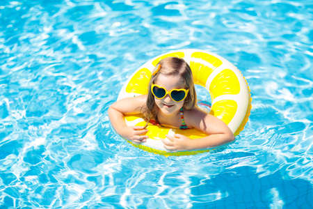 Child in swimming pool on inflatable yellow lemon ring. Little girl learning to swim with orange float. Water toy for baby and toddler. Healthy outdoor sport activity for children. Kids beach fun.