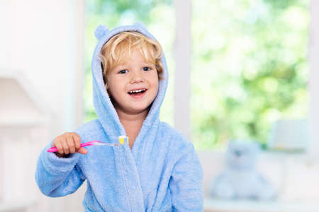 Child brushing teeth. Kids tooth brush and paste. Little baby boy in blue bath robe or towel brushing his teeth in white bathroom with window on sunny morning. Dental hygiene and heath for children. Stock Photo