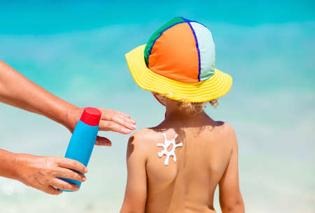 Mom applying sunscreen on child. Safe beach and sun tan fun. UV protection for young kid. Skin health care. Sun block spf cream and lotion for kids. Summer vacation with children. Archivio Fotografico