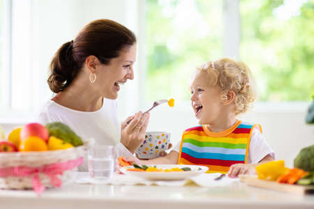 Mother feeding child vegetables. Mom feeds kid in white kitchen with window. Baby boy sitting in high chair eating healthy lunch of steamed carrot and broccoli. Nutrition, vegetarian diet for toddler Banque d'images