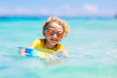 Child surfing on tropical beach. Family summer vacation in Asia. Kids swim in ocean water. Kid on surf body board. Little boy swimming in exotic sea. Travel with children. Water and beach sport.