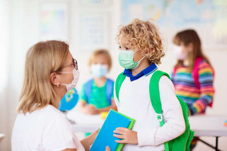 Teacher in class, school child in face mask during virus and flu outbreak. Boy and girl back to school after quarantine and lockdown. Group of kids in masks for virus prevention.