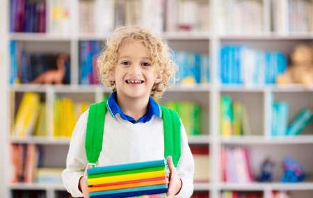 Child reading book. Kids read. Little boy at a colorful bookshelf doing homework for school. Student with books. Early education and development. Home library for children. Preschool kid study. Imagens