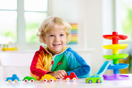 Little boy playing toy cars. Young kid with colorful educational vehicle and transport toys. Child driving car to rainbow parking garage. Kids at home or daycare. Kindergarten or preschool game. Archivio Fotografico