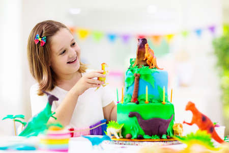 Kids birthday party. Dinosaur theme cake. Little girl blowing candles and opening gifts. Children event. Decoration for dinosaurs themed celebration. Stock Photo