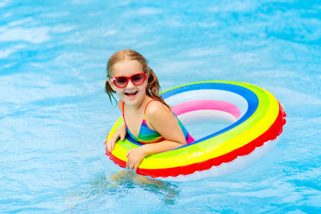 Child in swimming pool floating on toy ring. Kids swim. Colorful rainbow float for young kids. Little girl having fun on family summer vacation in tropical resort. Beach and water toys. Sun protection.