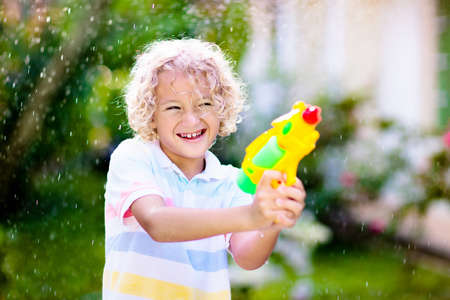 Kids play with water gun toy in garden. Outdoor summer fun. Little boy playing with water hose in sunny backyard. Party game for children. Healthy activity for hot sunny day.