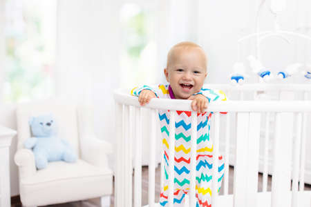 Cute laughing baby standing in bed after nap time. Nursery interior for young kids. Adorable little boy playing in his crib. White furniture for children bedroom. Stock Photo