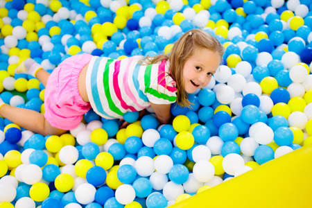 Child playing in ball pit. Colorful toys for kids. Kindergarten or preschool play room. Toddler kid at day care indoor playground. Balls pool for children. Birthday party for active preschooler. Banque d'images