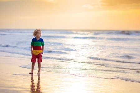 Child playing on ocean beach. Kid jumping in the waves at sunset. Sea vacation for family. Little boy running on exotic island during summer holiday. Reklamní fotografie