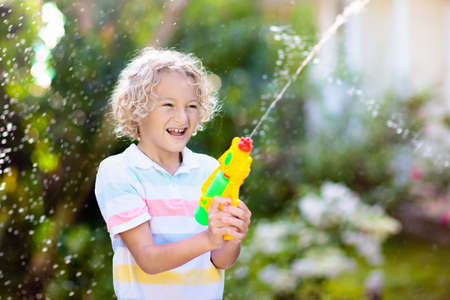 Kids play with water gun toy in garden. Outdoor summer fun. Little boy playing with water hose in sunny backyard. Party game for children. Healthy activity for hot sunny day. Reklamní fotografie