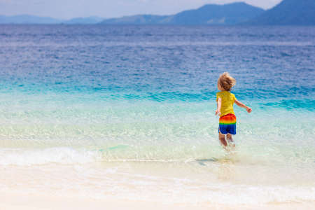 Kids playing on tropical beach. Children swim and play at sea on summer family vacation. Sand and water fun, sun protection for young child. Little boy and girl running and jumping at ocean shore. Reklamní fotografie