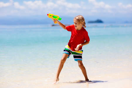 Child playing with toy water gun. Vacation and beach fun. Kids run and play with plastic pistol on tropical island resort. Family summer holiday activity at the sea. Travel with children.