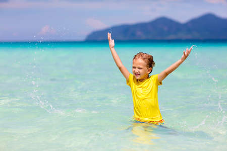 Kids playing on tropical beach. Children swim and play at sea on summer family vacation. Sand and water fun, sun protection for young child. Little boy running and jumping at ocean shore.