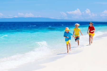 Kids playing on tropical beach. Children swim and play at sea on summer family vacation. Sand and water fun, sun protection. Little child running and jumping at ocean shore.