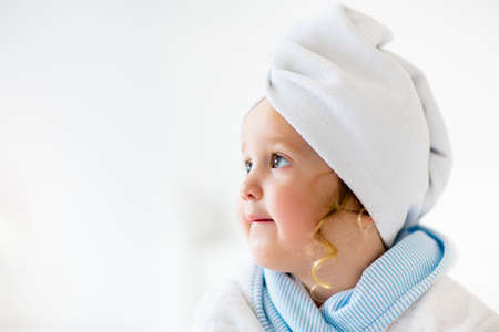 Baby girl in towel after bath. Infant care. Little child wrapped in warm robe after shower. Washed clean kid on bed before sleep. Bedding and textile for children. Kids hygiene and washing products.
