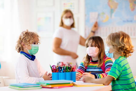 Teacher in class, school child in face mask during flu outbreak. Boy and girl back to school after quarantine and lockdown. Group of kids in masks for prevention. Reklamní fotografie