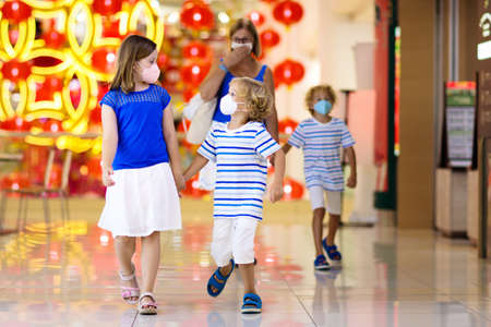 Family wearing face mask in shopping mall in Asia. Mother and children wear facemask during virus and flu outbreak. Virus and illness protection. Kids in masks in public crowded place.