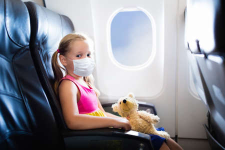 Child in airplane in face mask. Virus outbreak. virus and flu pandemic. Safe travel with young child and baby. Kids flying airplane in surgical masks.