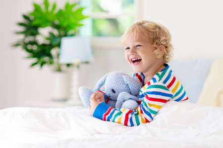 Child playing in bed in white sunny bedroom with window. Kids room and interior design. Baby boy at home. Bedding and textile for children nursery. Kid with toy and book. Nap and sleep time. Reklamní fotografie