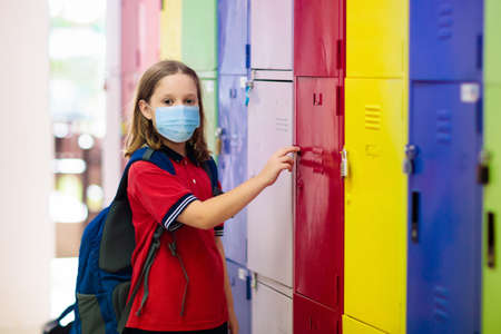 School child wearing face mask during virus and flu outbreak. Girl going back to school after quarantine and lockdown. Kids in masks for  prevention.