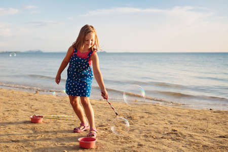Kids blow bubbles at tropical beach. Child blowing soap bubble playing at sea. Family summer vacation with young kid. Outdoor beach activity for children. Water and sand toys for baby or toddler.