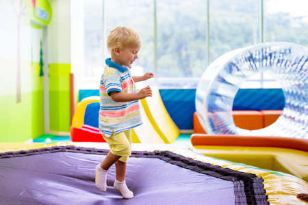 Child jumping on colorful playground trampoline. Kids jump in inflatable bounce castle on kindergarten birthday party Activity and play center for young child. Little boy playing indoor.