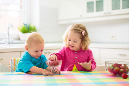 Child having breakfast. Kid drinking milk and eating cereal with fruit. Little boy and girl at white dining table in kitchen at window. Kids eat on sunny morning. Healthy balanced nutrition for kids.