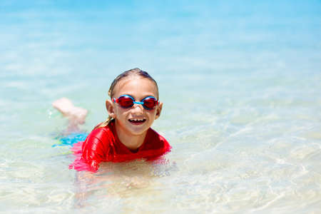Kids run and play on tropical beach. Children swim and jump in sea on summer family vacation. Sand and water fun, sun protection for young child. Little boy running and jumping at ocean shore.