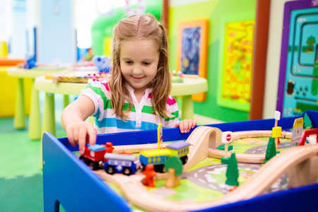 Kids play toy railroad. Little girl with wooden trains in indoor playground or amusement center. Child with car and train toys at home or daycare. Kindergarten or preschool play room.