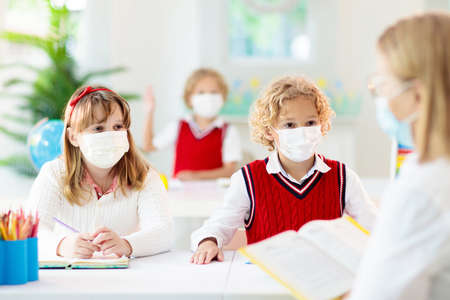 Kids in face mask in school class. Child back to school after virus lockdown. Primary child in pandemic. Safety and virus spread prevention. Student in surgical mask. Social distancing.