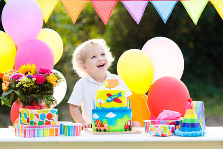 Kids birthday party. Child blowing out candles on colorful cake. Decorated garden with rainbow flag banners, balloons. Car and airplane theme celebration. Little boy celebrating birthday. Party food.