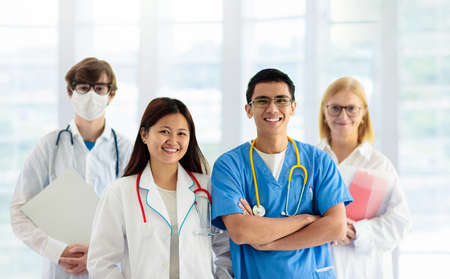 International doctor team. Hospital medical staff. Mixed race Asian and Caucasian doctor and nurse meeting. Clinic personnel wearing face mask and stethoscope. virus outbreak.