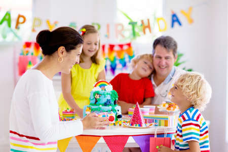 Kids birthday party. Child blowing candles on cake and opening presents on jungle theme celebration. Family celebrating at home. Mother, father, boy and girl open gifts, eat cakes. Sweets for children