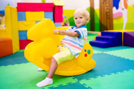 Child riding toy horse. Little boy playing with rocking toy. Kid in indoor playground or kindergarten. Toddler at day care play room. Toys for little boys. Daycare amusement center. Reklamní fotografie