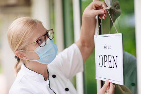 Cafe opening after lockdown. Open sign on front door of restaurant or grocery store. Waiter in apron greeting customer. Welcome message on bakery entrance. Back to work after quarantine.