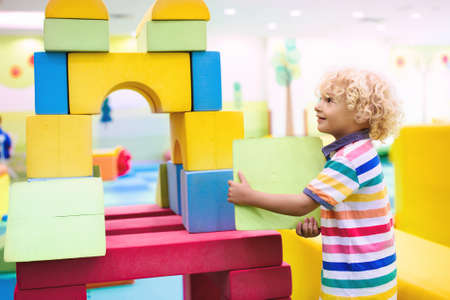 Child playing with colorful construction toy blocks. Educational toys for young kids. Kindergarten or preschool play room. Toddler kid at day care playground. Girl building house with block at daycare