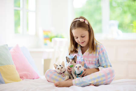 Child playing with baby cat on bed in white bedroom. Kid holding white kitten. Little girl in pajamas with cute pet animal at home. Kids play with cats. Children and domestic animals pets. Reklamní fotografie