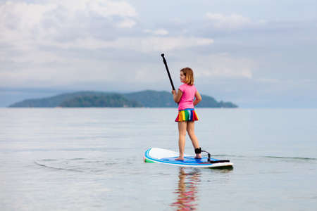 Child on stand up paddle board. Water fun and beach sport for kids. Healthy outdoor sports for summer vacation on tropical island. Holiday activity. Fit little girl training. Surfer exercising. Reklamní fotografie