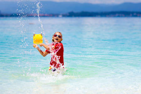 Kids playing on tropical beach. Water splash fun. Little boy splashing in sea waves. Children swim and play on summer family vacation. Sand and water toy, sun protection for young child.