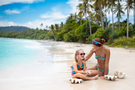 Mother and child on tropical beach. Sun screen for kids. Mom applying sun protection lotion on little girl. Safe tan. Family summer vacation on exotic island with palm trees.