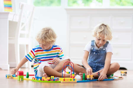 Kids play with wooden railway. Child with toy train. Educational toys for young children. Little boy building railroad tracks on white floor at home or kindergarten. Cute kid playing cars and engine. Reklamní fotografie