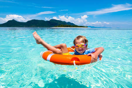 Child with inflatable ring on beautiful beach. Little boy swimming in exotic sea. Ocean vacation with kid. Children play on summer beach. Water fun. Kids swim. Family holiday on tropical island. Reklamní fotografie